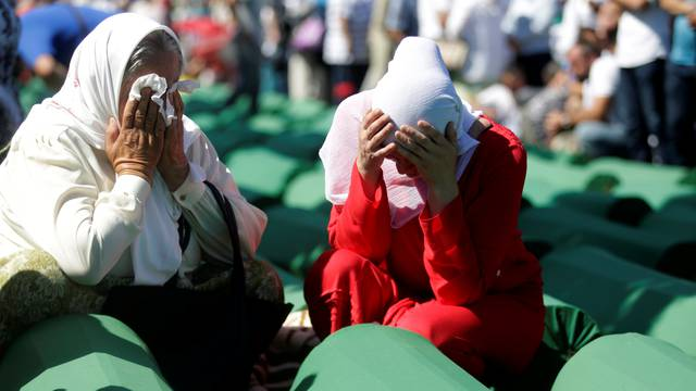 Muslim women cry near coffins of their relatives, who are newly identified victims of the 1995 Srebrenica massacre, which are lined up for a joint burial in Potocari near Srebrenica