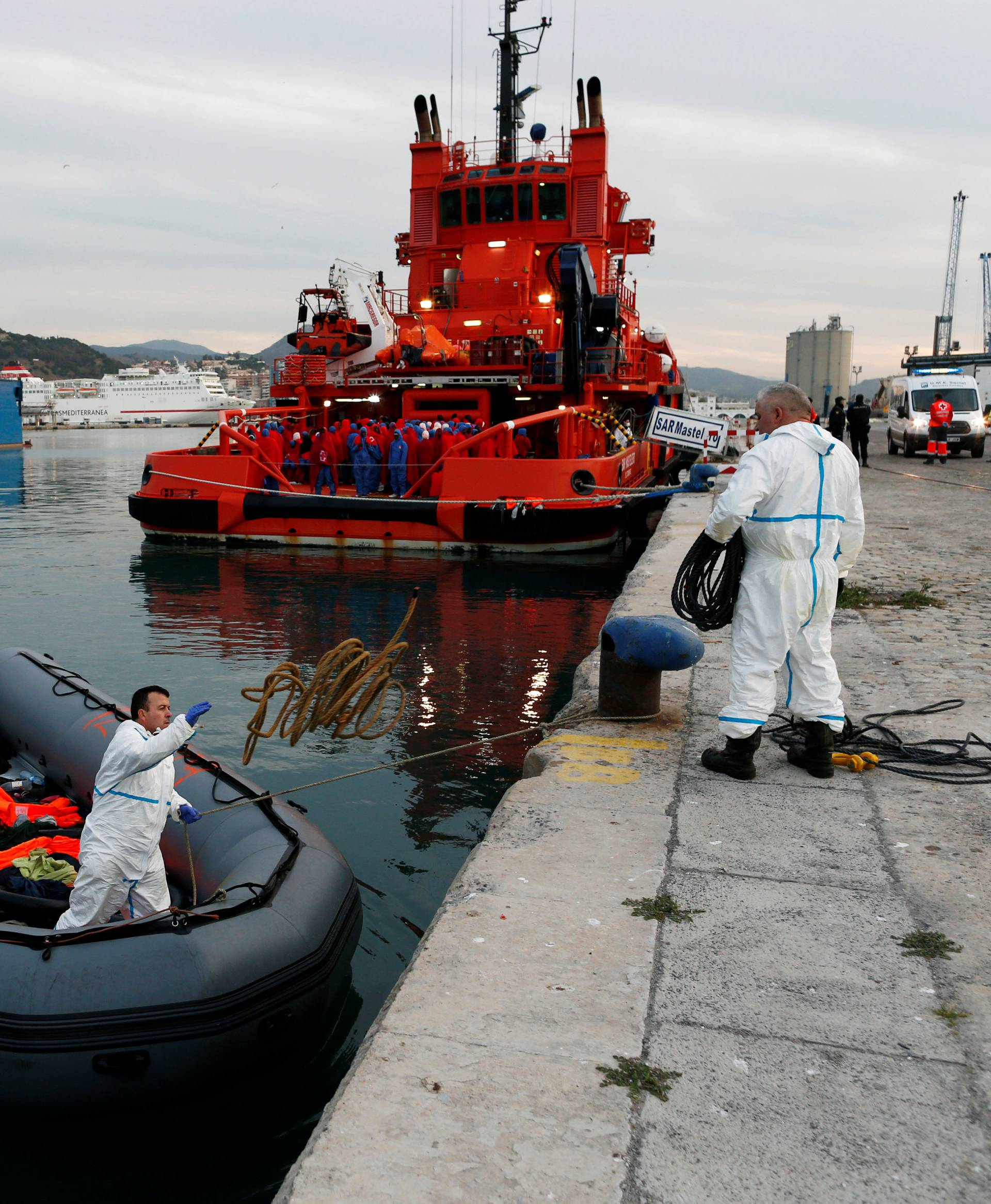 Migrants wait to disembark from a rescue boat as they watch as rescuers remove their floats and life-vests from a dinghy at dawn at the port of Malaga