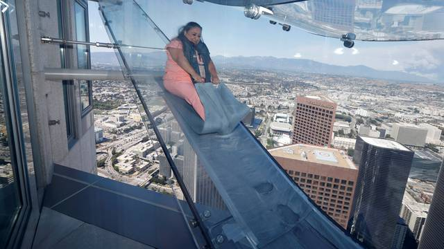 Patricia Rodriguez, 49, rides the Skyslide on the 69th and 70th floors of the U.S. Bank Tower which is attached to the OUE Skyspace LA observation deck in downtown Los Angeles