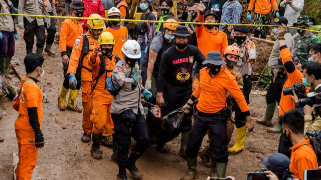 Indonesian rescuers carry a body bag during the search for victims buried by landslides in Sumedang