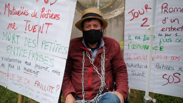 Martial Leotard, General Director of Les Ducs de Richelieu society, is seen chained in front of the Mutuelle de Poitiers Assurance, in Liguge