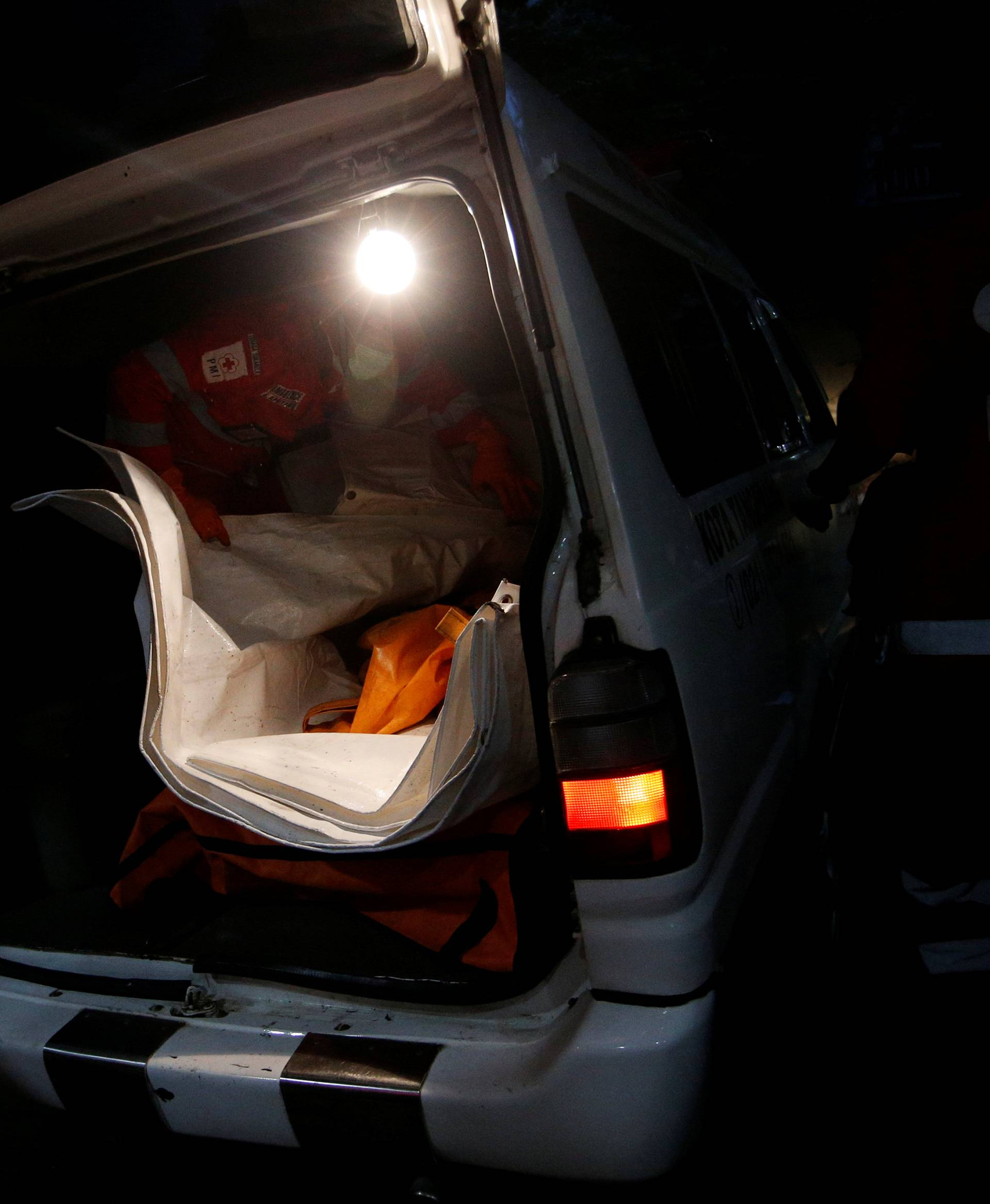 Officials carry a body bag off an ambulance to be identified by Indonesian Disaster Victim Identification (DVI) officer at Bhayangkara R. Said Sukanto hospital in Jakarta