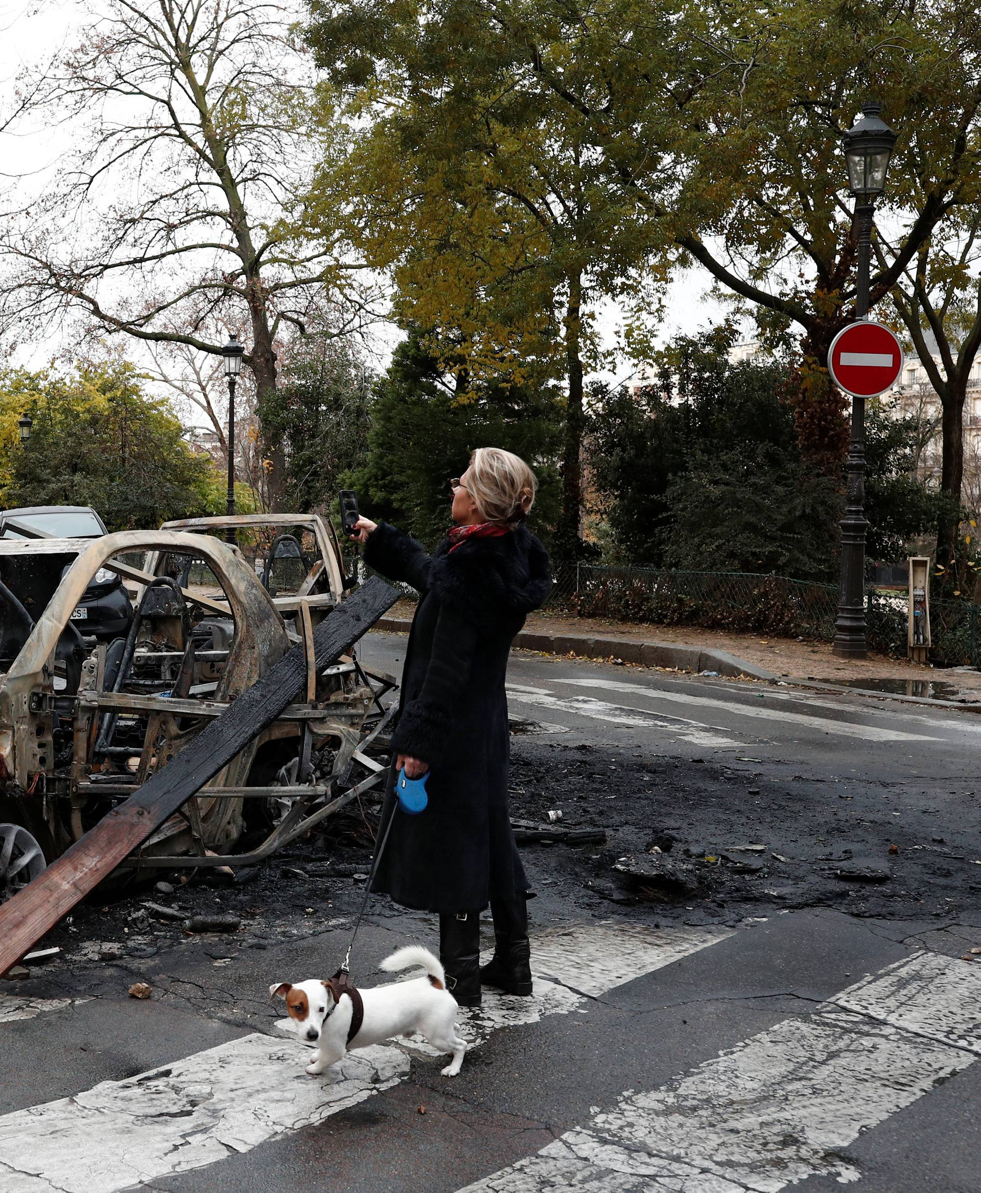Vandalized cars are seen on a street the morning after clashes with protesters wearing yellow vests, a symbol of a French drivers' protest against higher diesel taxes, in Paris