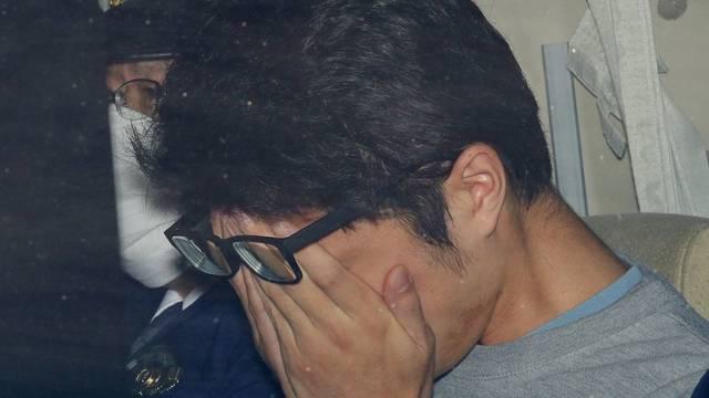 Takahiro Shiraishi covers his face inside a police car in Tokyo