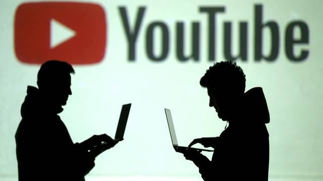 FILE PHOTO: FILE PHOTO: Silhouettes of mobile device users are seen next to a screen projection of Youtube logo in this picture illustration