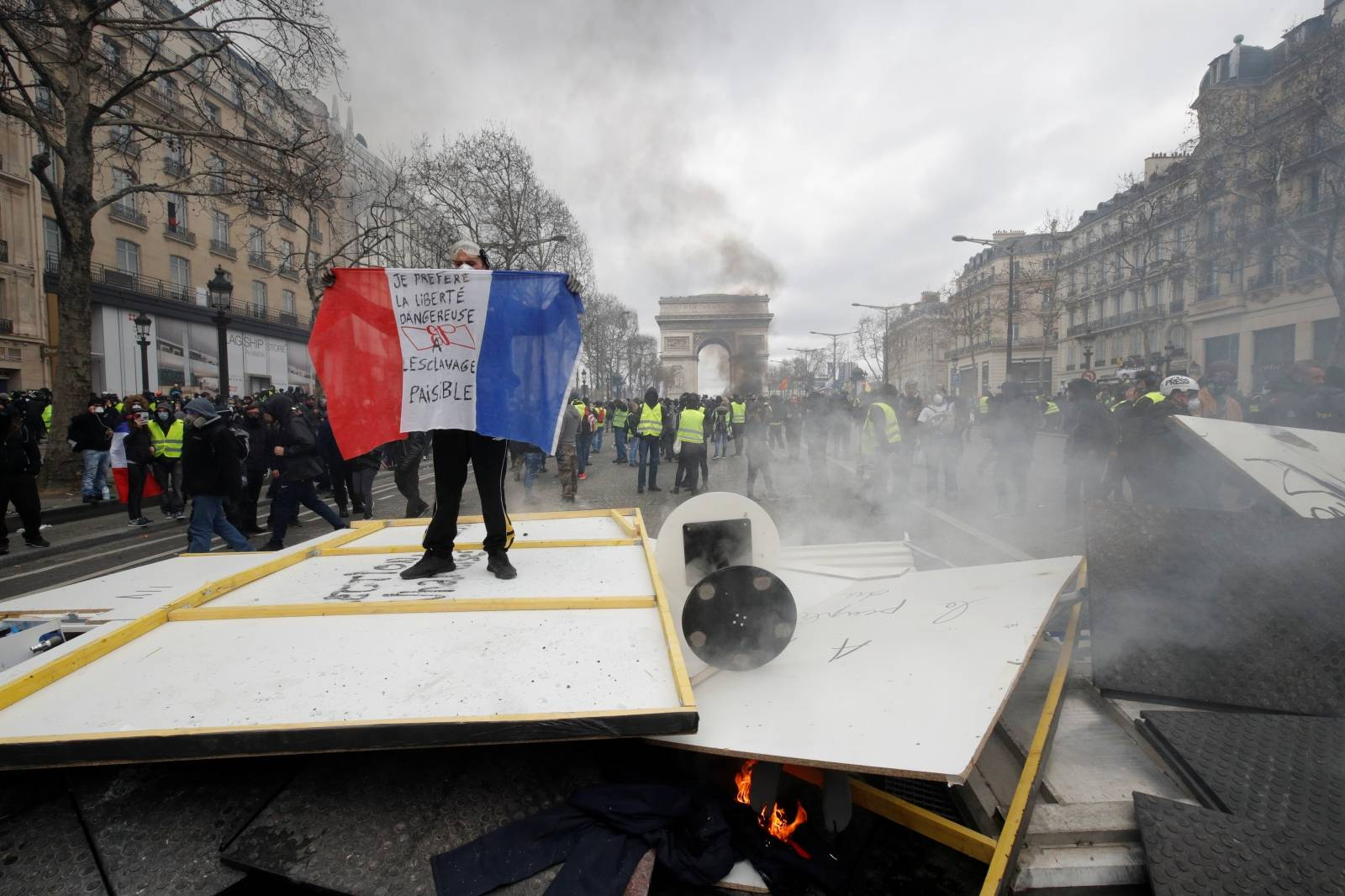 """A protester holds a flag as he stands on a barricade during a demonstration by the """"yellow vests"""" movement in Paris"""