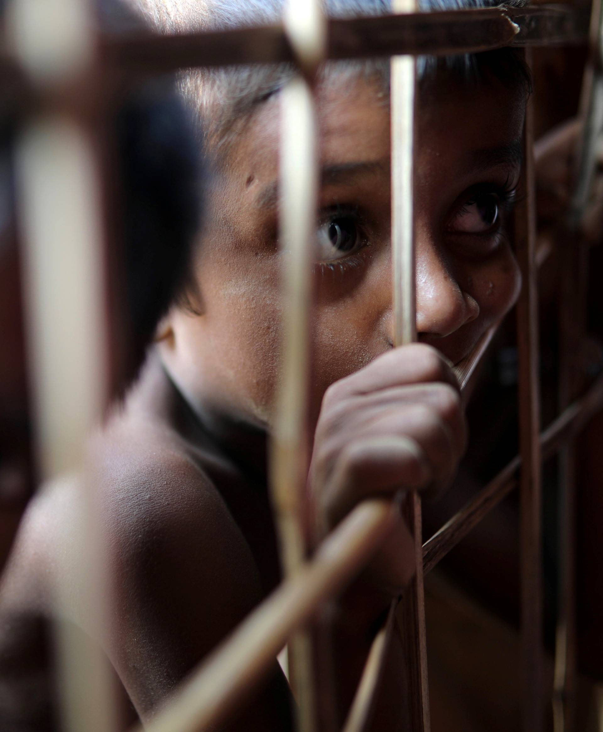 Rohingya refugee child looks through the fence at a refugee camp in Cox's Bazar