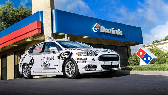 A Ford self-driving delivery vehicle is pictured in front of a Domino's pizza restaurant in this handout photo