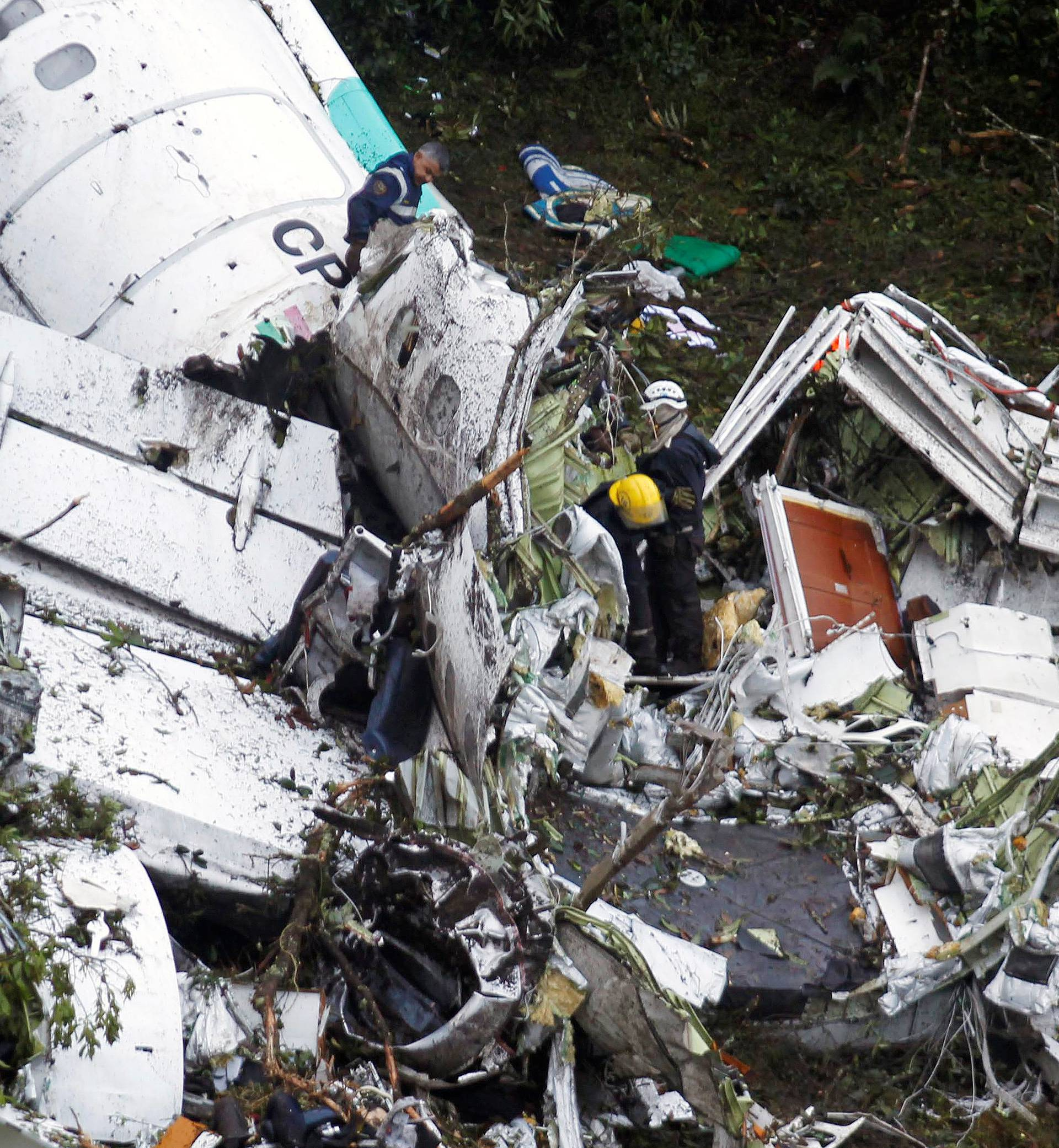 Rescue crew work in the wreckage from a plane that crashed into Colombian jungle with Brazilian soccer team Chapecoense near Medellin