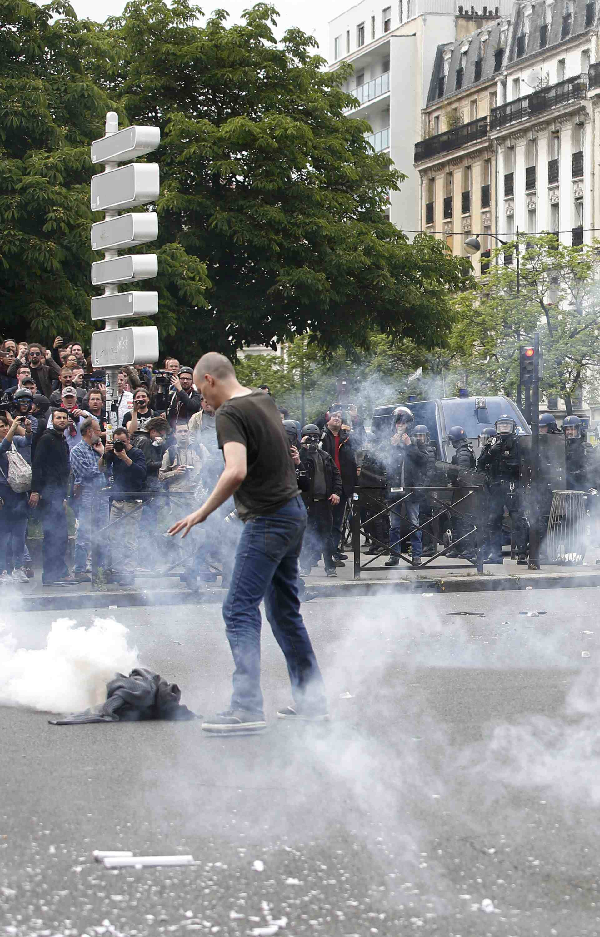 Tear gas fills the air during clashes with French gendarmes during a demonstration in protest of the government's proposed labor law reforms in Paris