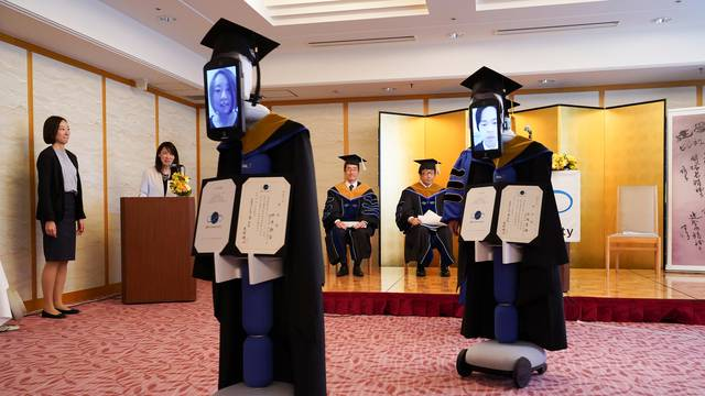 Ipads attached to 'newme' robots replacing graduating students' presence at a ceremony, wear graduation gowns and hats in Tokyo