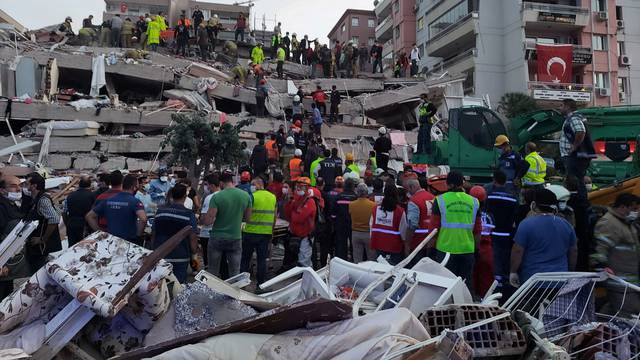 People search for survivors at a collapsed building after a strong earthquake struck the Aegean Sea where some buildings collapsed in the coastal province of Izmir
