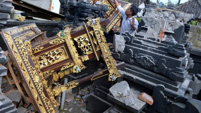 A man is seen among damaged buildings of a temple after a 4.8 magnitude earthquake struck northeast of Bali