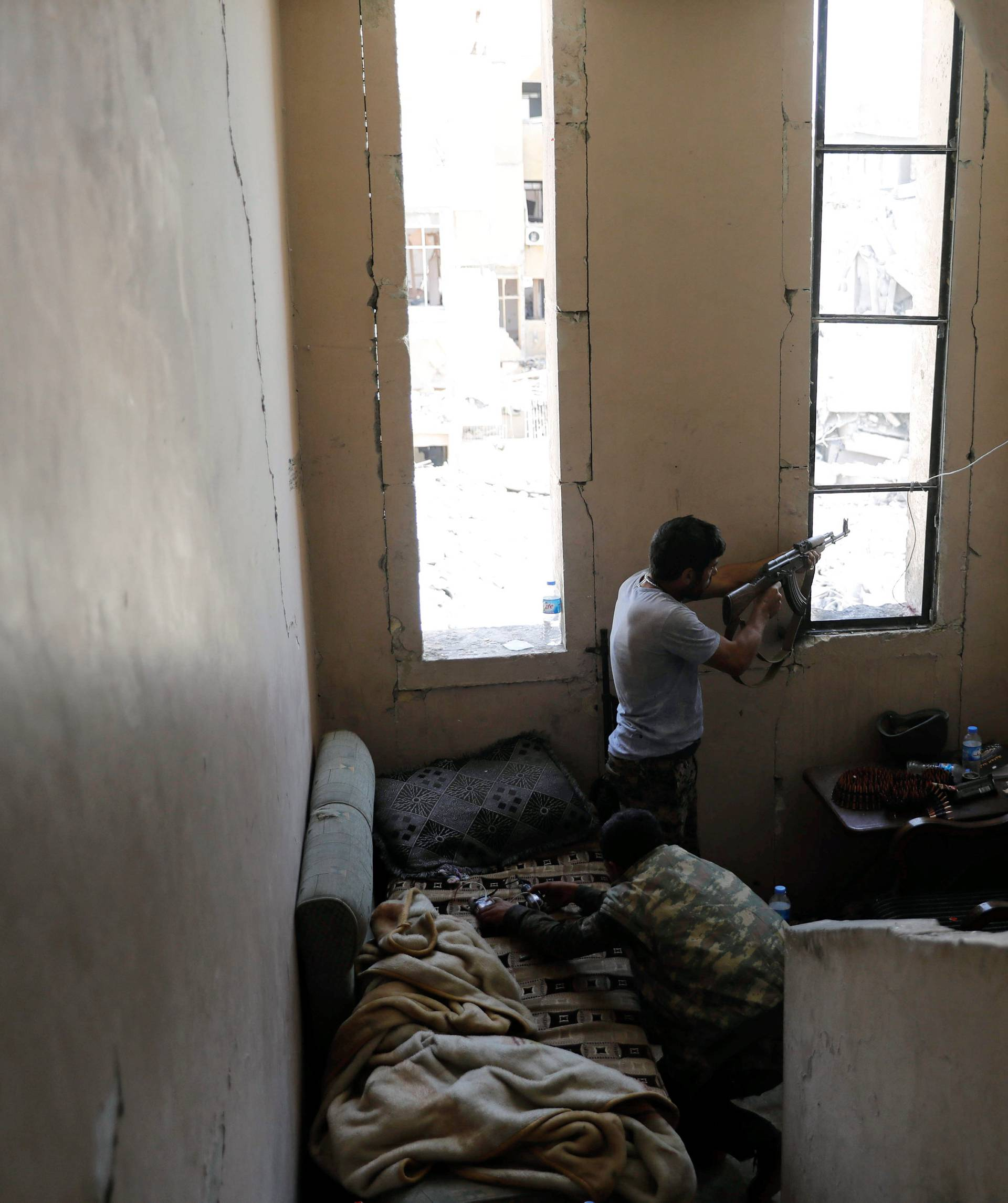A fighter of the Syrian Democratic Forces fires his weapon towards the positions of the Islamic state militants in the National Hospital, at the frontline in Raqqa