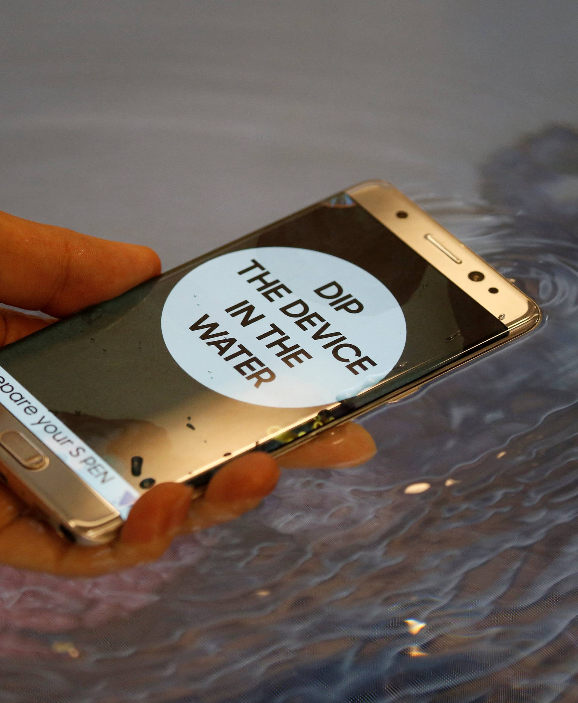 A model demonstrates waterproof function of Galaxy Note 7 new smartphone during its launching ceremony in Seoul
