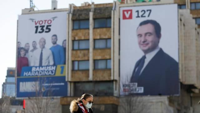 Woman wearing a mask walks near electoral campaign billboards in Pristina