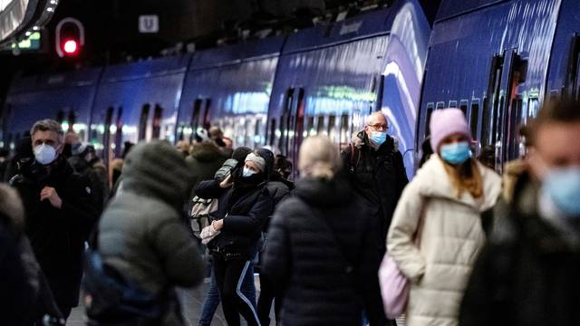 Passengers wearing protective masks walk on a platform at Malmo Central Station amid the coronavirus disease (COVID-19) outbreak in Malmo