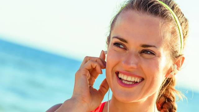happy fit woman on seacoast with headphones listening to music
