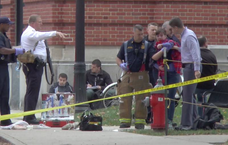 A girl is led to an ambulance by emergency personnel following an attack at Ohio State University's campus in Columbus