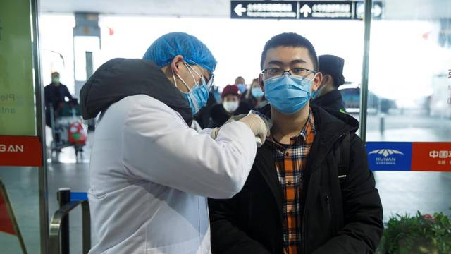 A medical official takes the body temperature of a man at the departure hall of the airport in Changsha