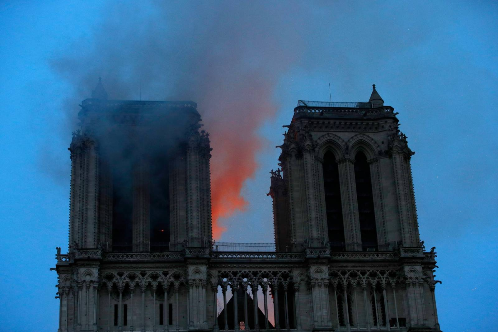 Smoke and flames fill the sky as a fire burns at the Notre Dame Cathedral during the visit by French President Emmanuel Macron (not pictured) in Paris
