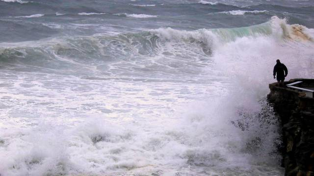 A man looks over cliff as large waves batter coastline near Coogee Beach in Sydney