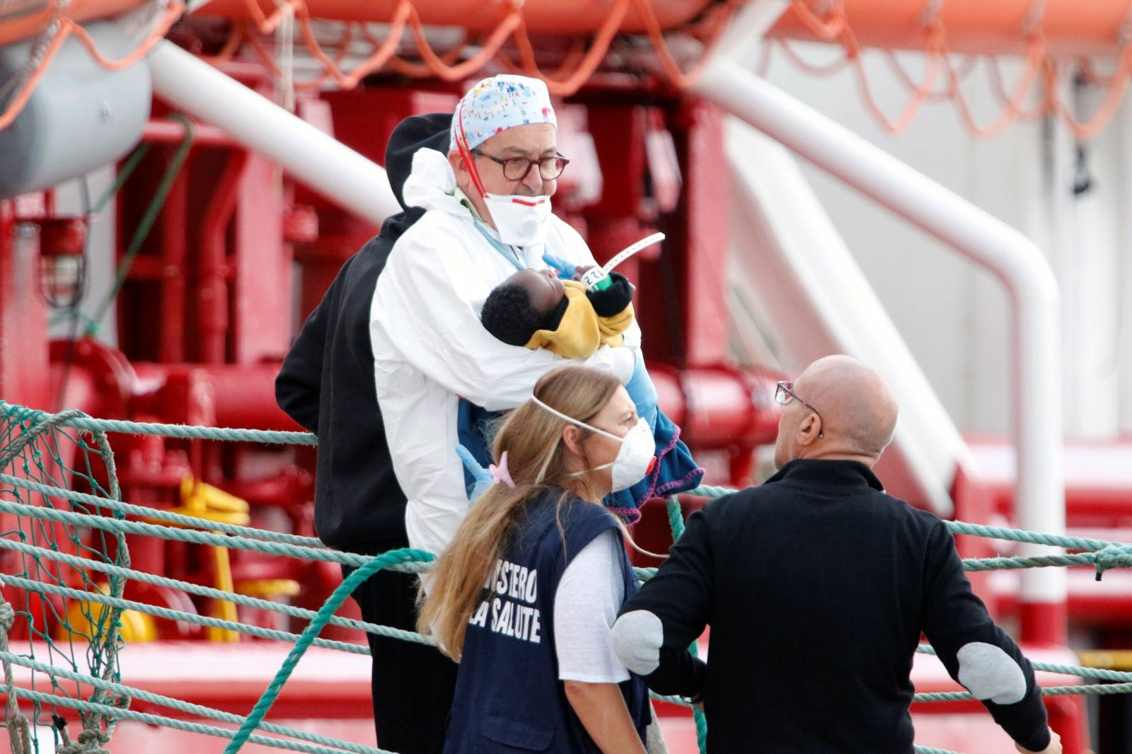 An Italian doctor at the Pozzallo port, Vincenzo Morello carries a child as migrants disembark at the port after spending nearly two weeks on board the Medecins Sans Frontieres (MSF)-operated Ocean Viking