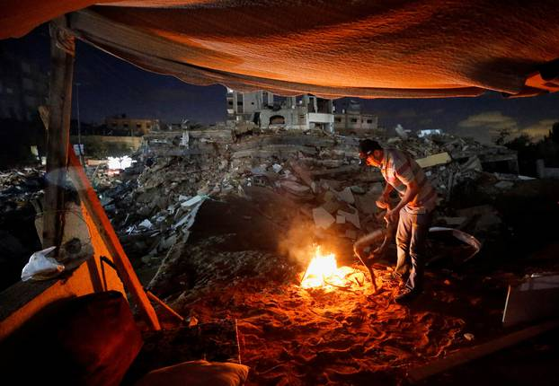 A Palestinian man lights a fire amid the rubble of his house which was destroyed by Israeli air strikes during the Israel-Hamas fighting in Gaza