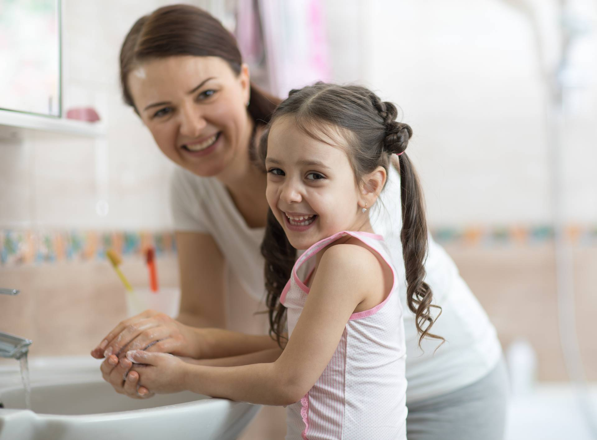 kid with mom washing her hands in bathroom