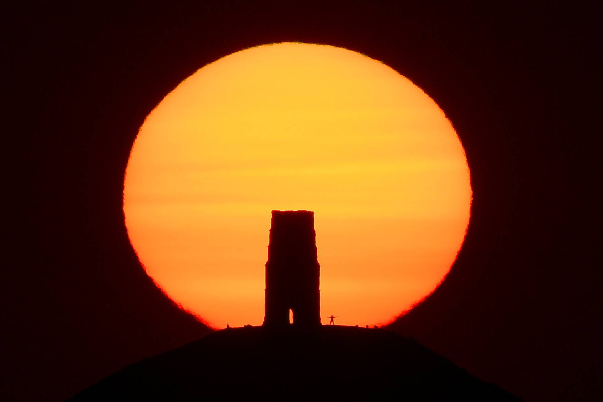 A person views the sun rise from beside the remains of Saint Michael's Church on top of Glastonbury Tor, in Glastonbury