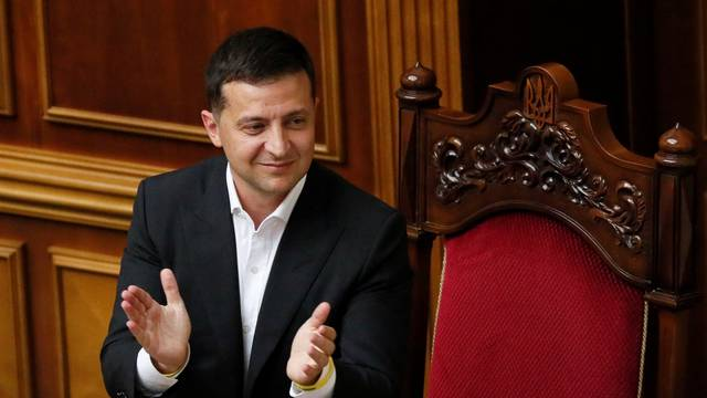 Ukrainian President Volodymyr Zelenskiy applauds during a session of parliament in Kiev