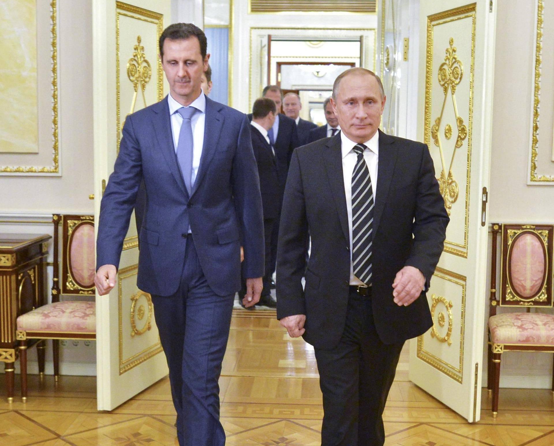 Russian President Vladimir Putin and Syrian President Bashar al-Assad enter a hall during a meeting at the Kremlin