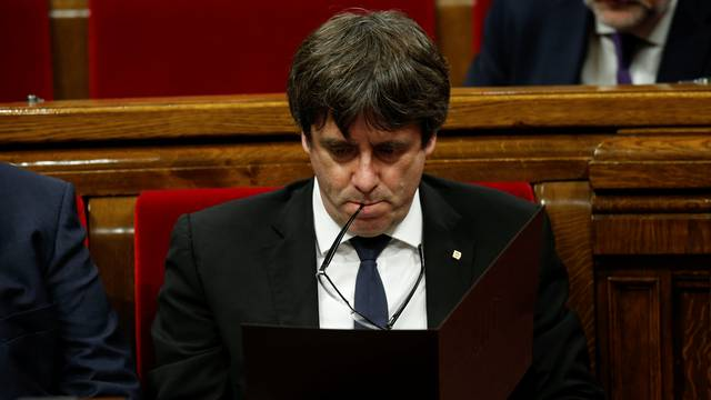 Catalan President Carles Puigdemont reviews his notes at the start of a plenary session at the Catalonian regional parliament in Barcelona