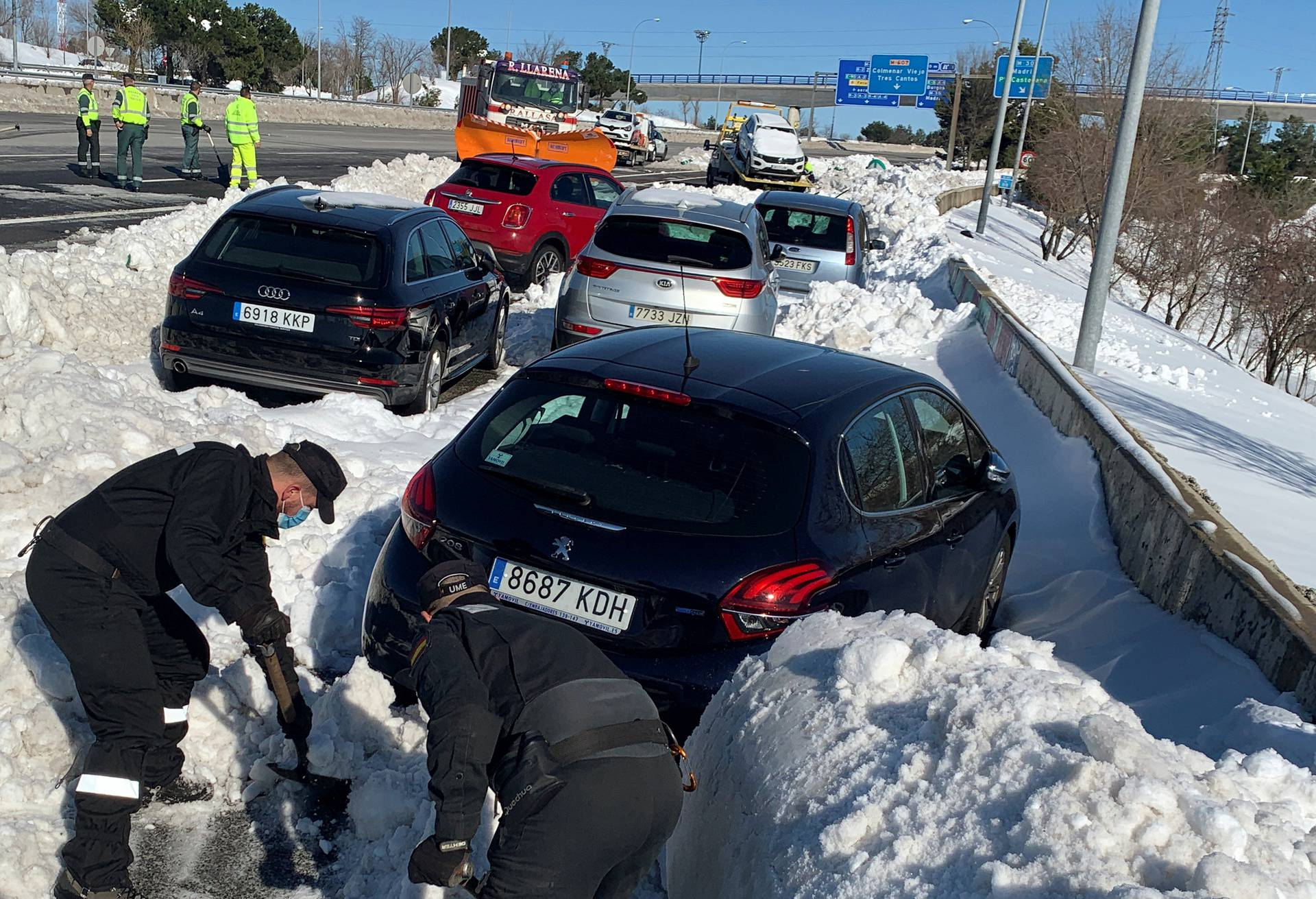 Members of Spain's military unit (UME) shovel snow to open a pass next to cars accumulated on M-40 highway after heavy snowfall in Madrid
