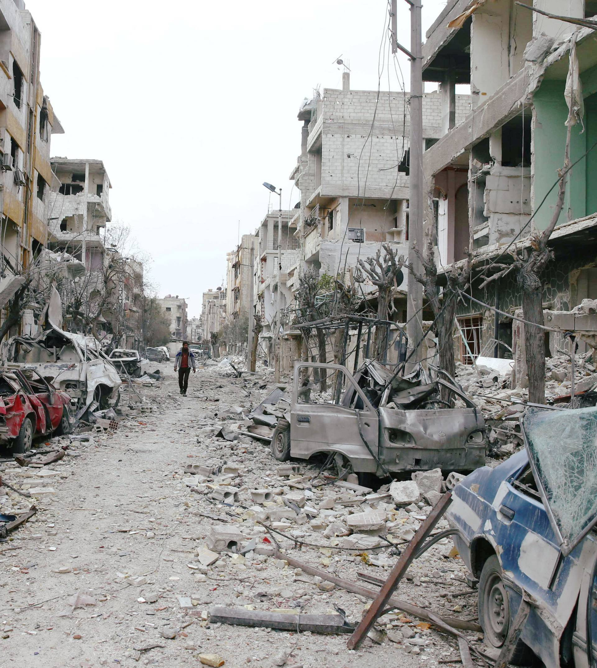 Damaged cars and buildings are seen in the besieged town of Douma, Eastern Ghouta, Damascus