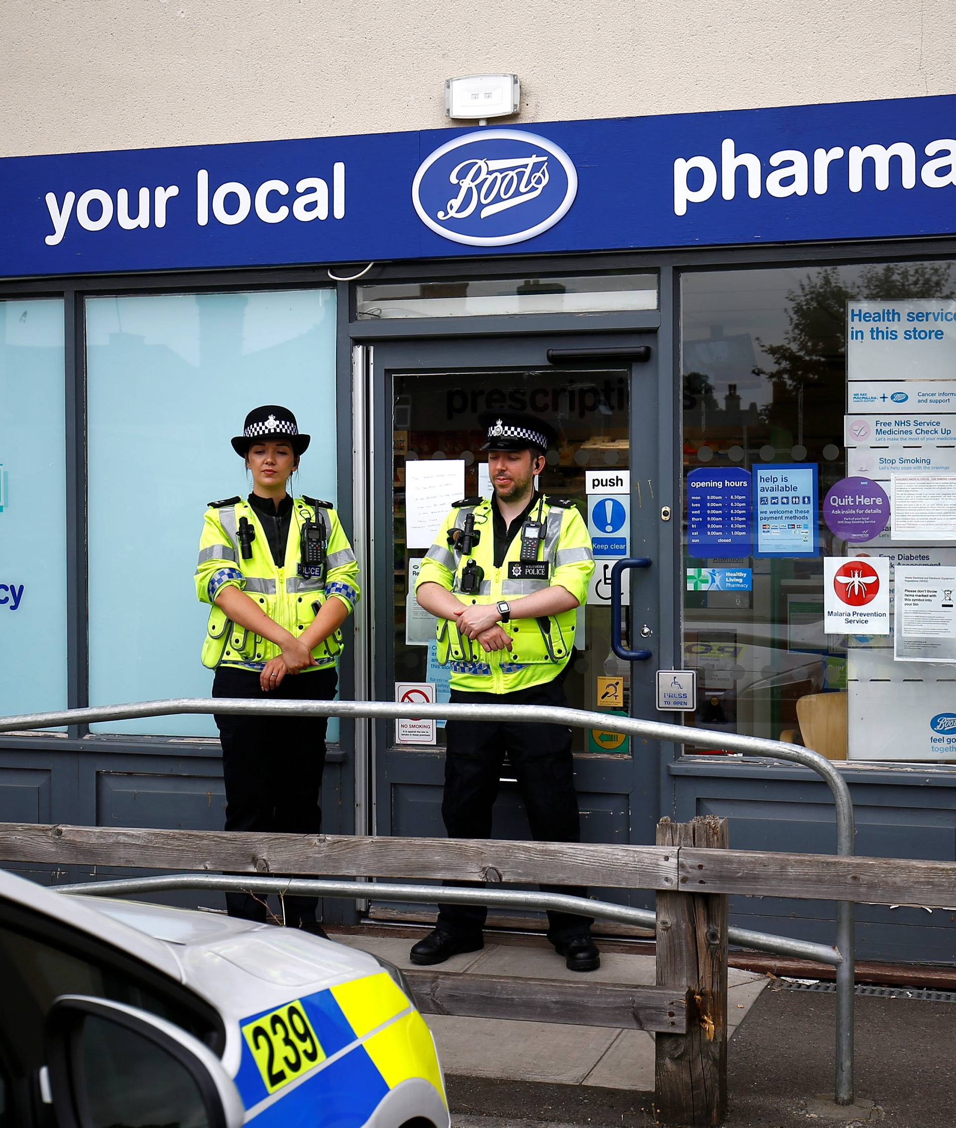 Police officers guard outside a branch of Boots pharmacy, which has been cordoned off after two people were hospitalised and police declared a 'major incident', in Amesbury