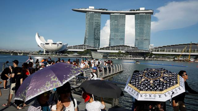 Tourists shield themselves with umbrellas from the sun in Singapore