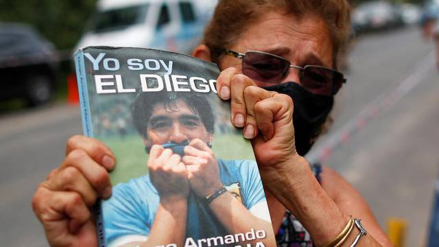 "Woman holds a book ""Yo soy el Diego"" outside the house where Diego Maradona was staying, in Tigre"