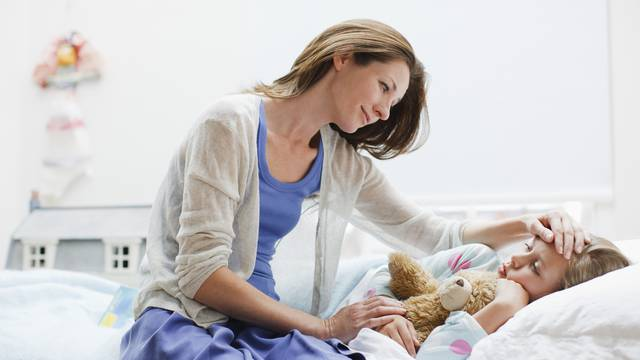 Mother checking on sick daughter laying in bed