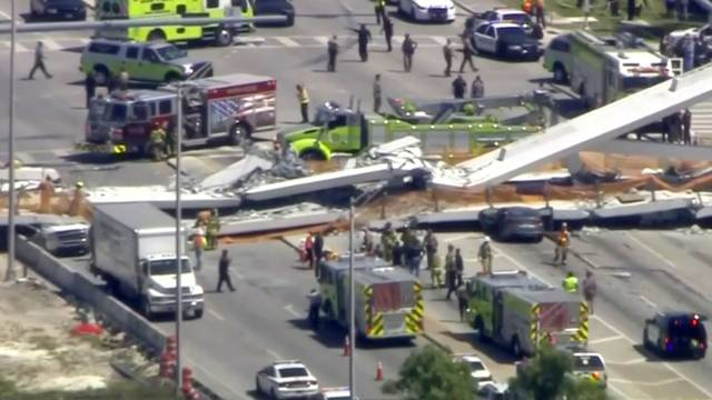 Emergency crews look for victims at the scene of a collapsed pedestrian bridge at Florida International University in Miami, Florida