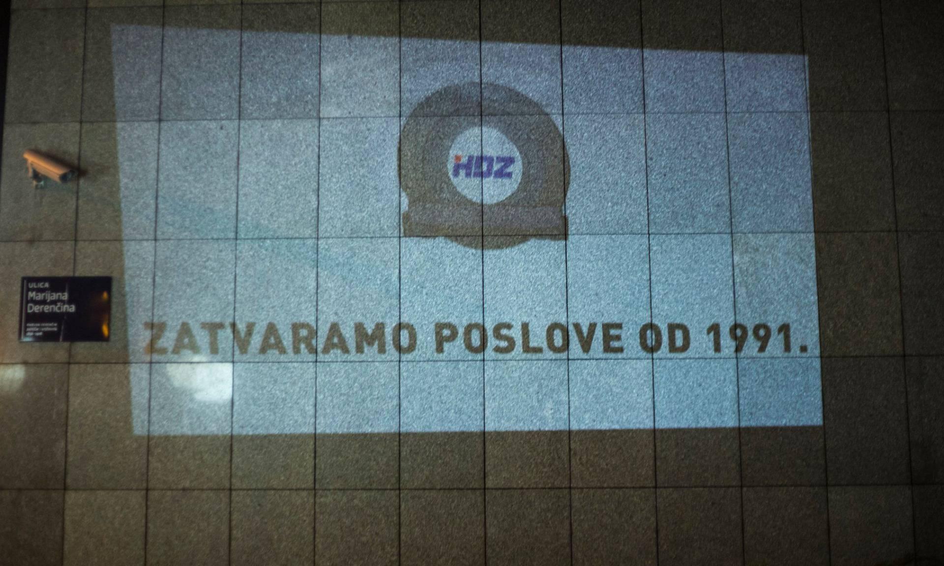 Projektorom na zgradi: 'HDZ, Zatvaramo poslove od 1991.'