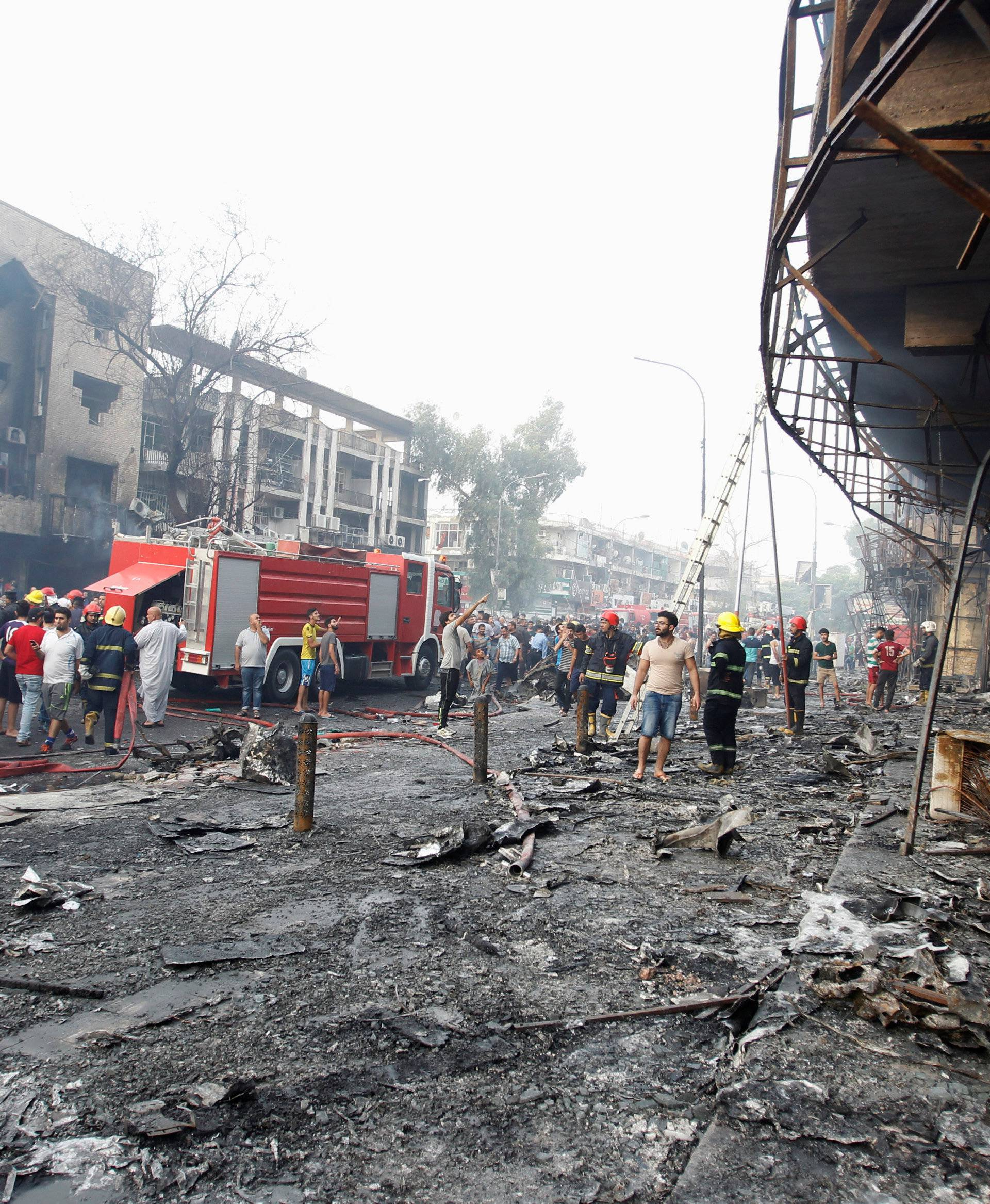 People inspect the site of a suicide car bomb in the Karrada shopping area, in Baghdad