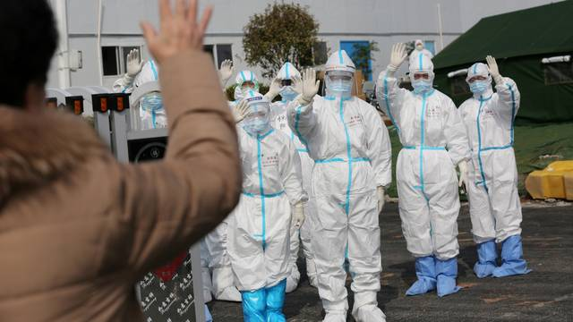 FILE PHOTO: Medical personnel in protective suits wave hands to a patient who is discharged from the Leishenshan Hospital after recovering from the novel coronavirus, in Wuhan