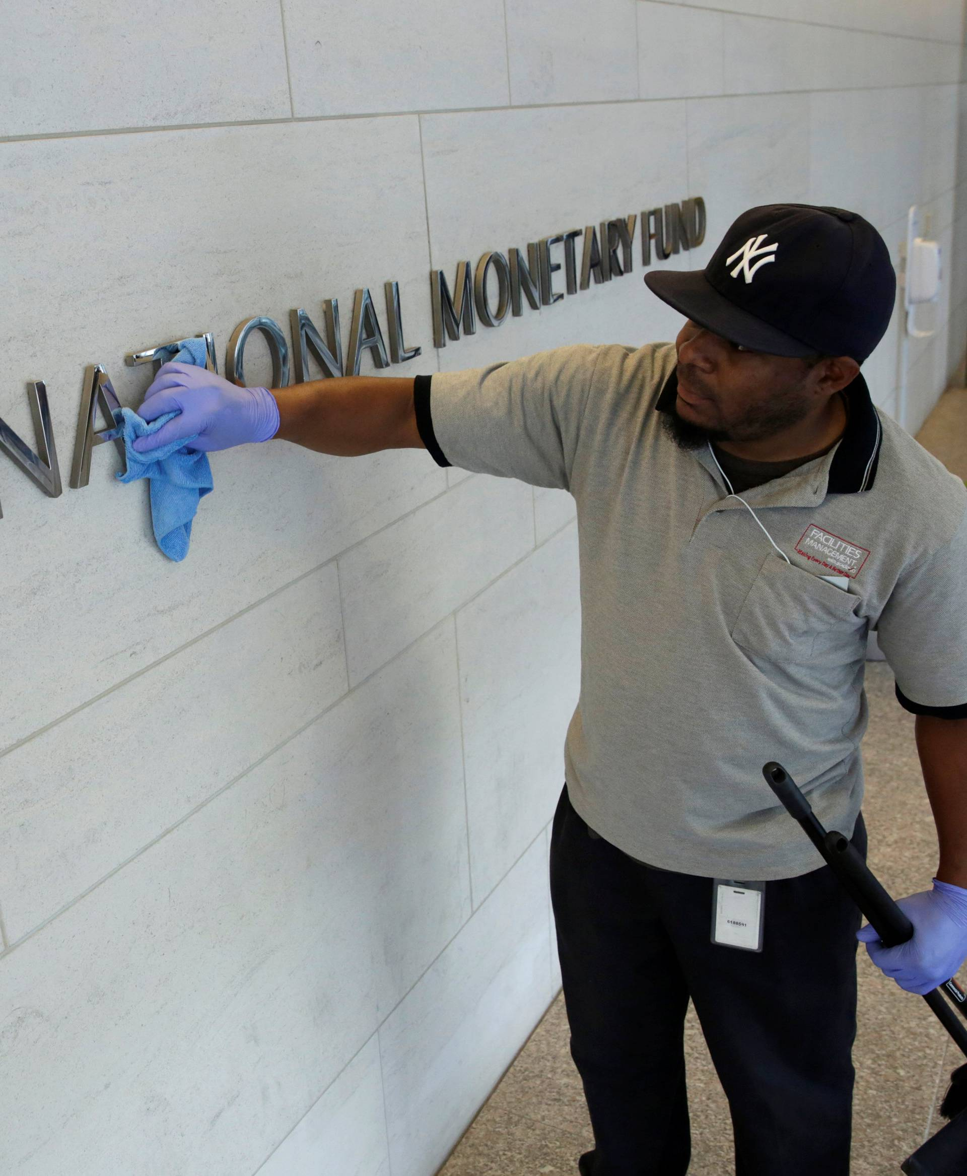Staff cleans signage at International Monetary Fund headquarters in Washington