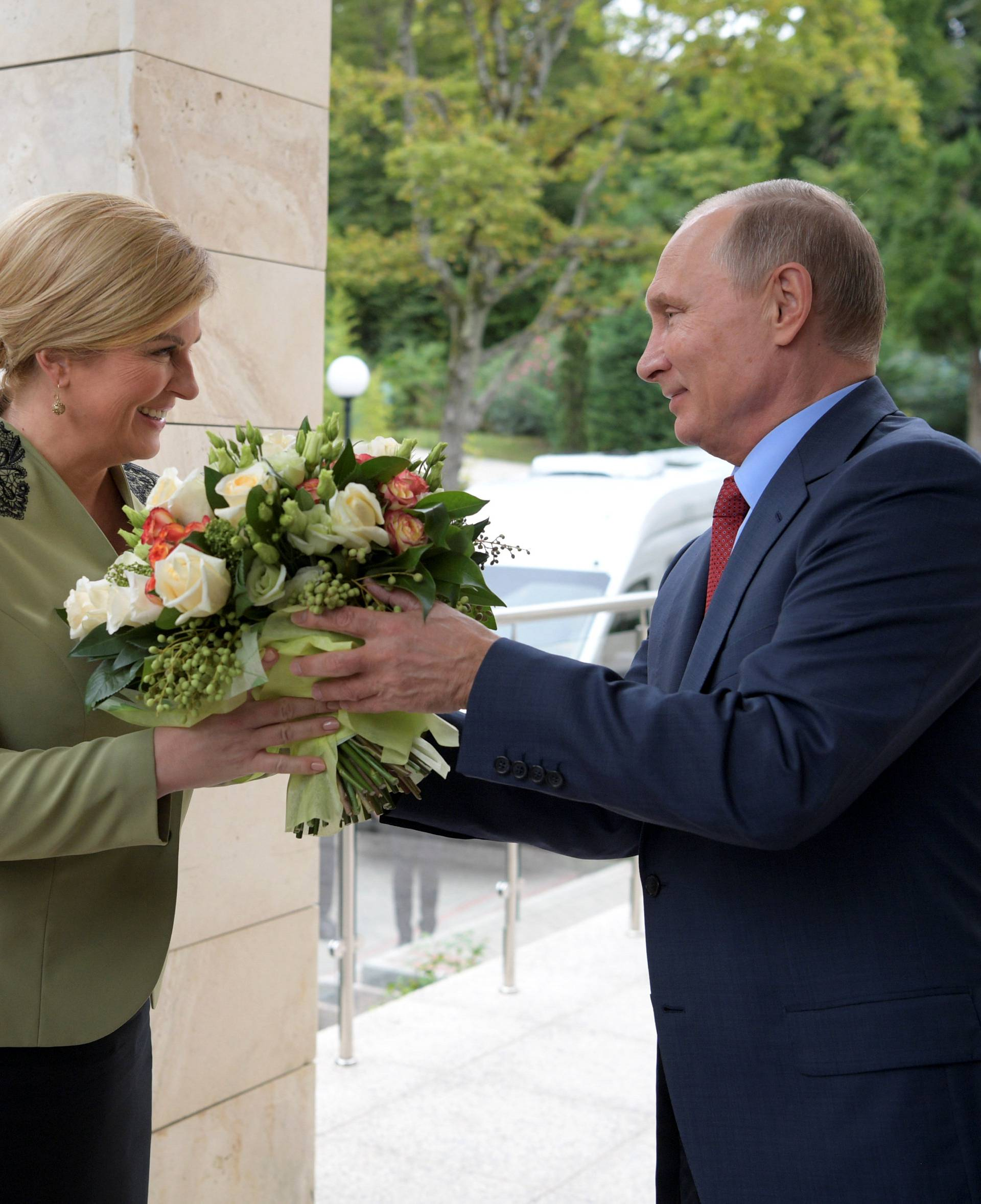 Russian President Vladimir Putin presents flowers to Croatian President Kolinda Grabar-Kitarovic during their meeting at the Bocharov Ruchei state residence in Sochi