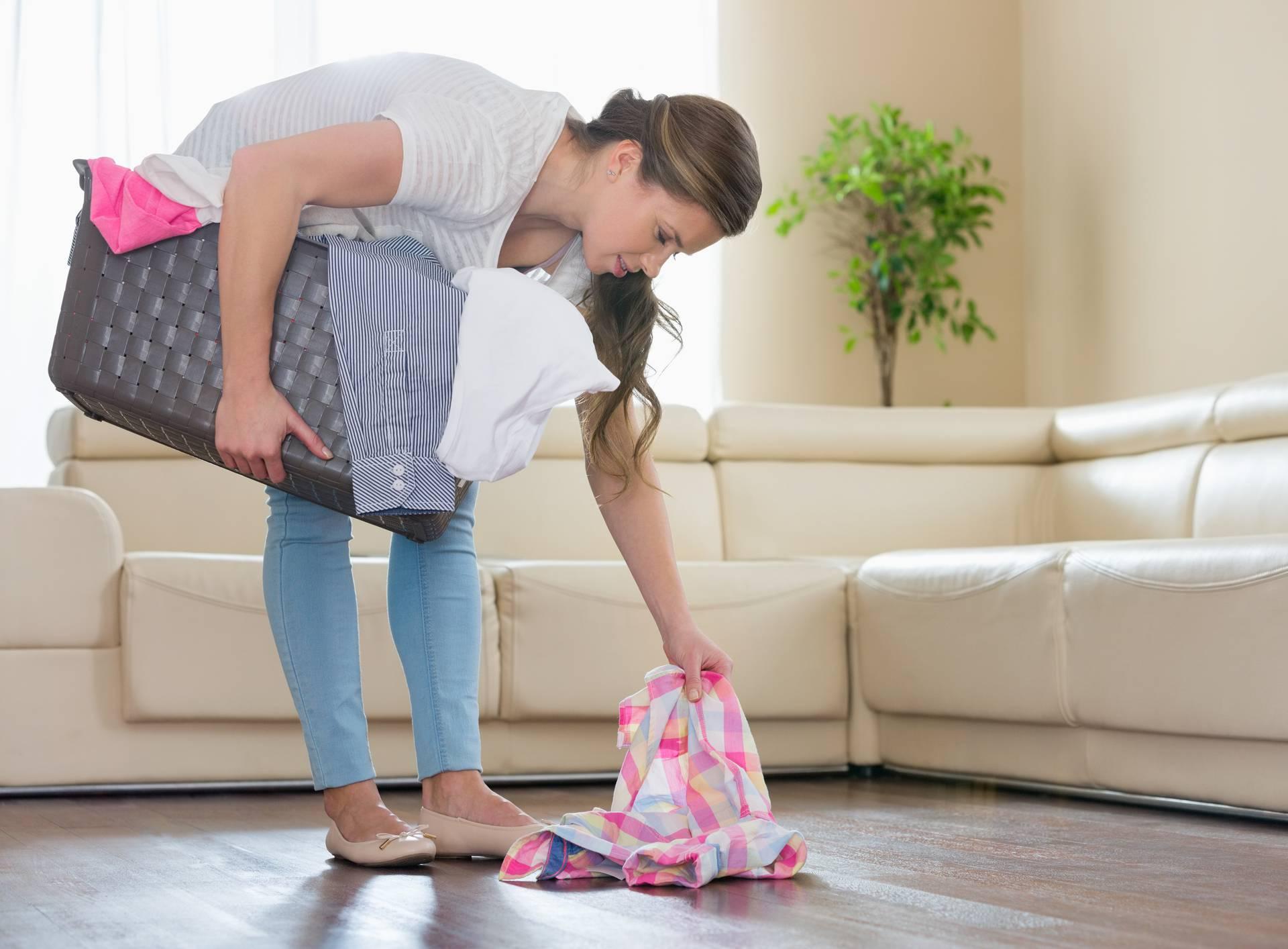 Žena diže i posprema košulju s poda