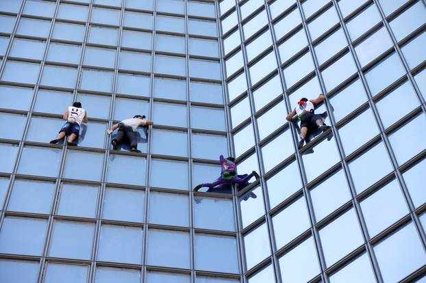 French Spiderman Alain Robert and climbers Martin Banot, Alexis Landot and Leo Urban climb a skyscraper in La Defense near Paris