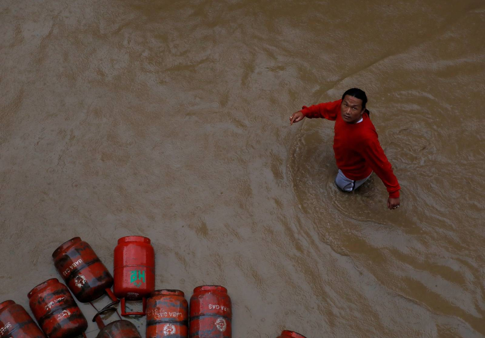 FILE PHOTO: A man walks past gas cylinders in a flooded colony in Kathmandu