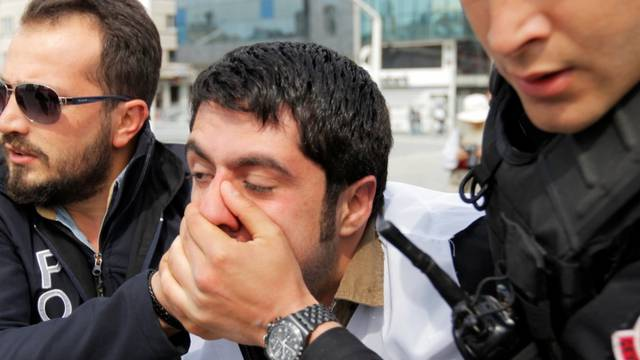 Plainclothes police officers detain a protester as he and others attempt to defy a ban and to gather at Taksim Square to celebrate May Day, in central Istanbul
