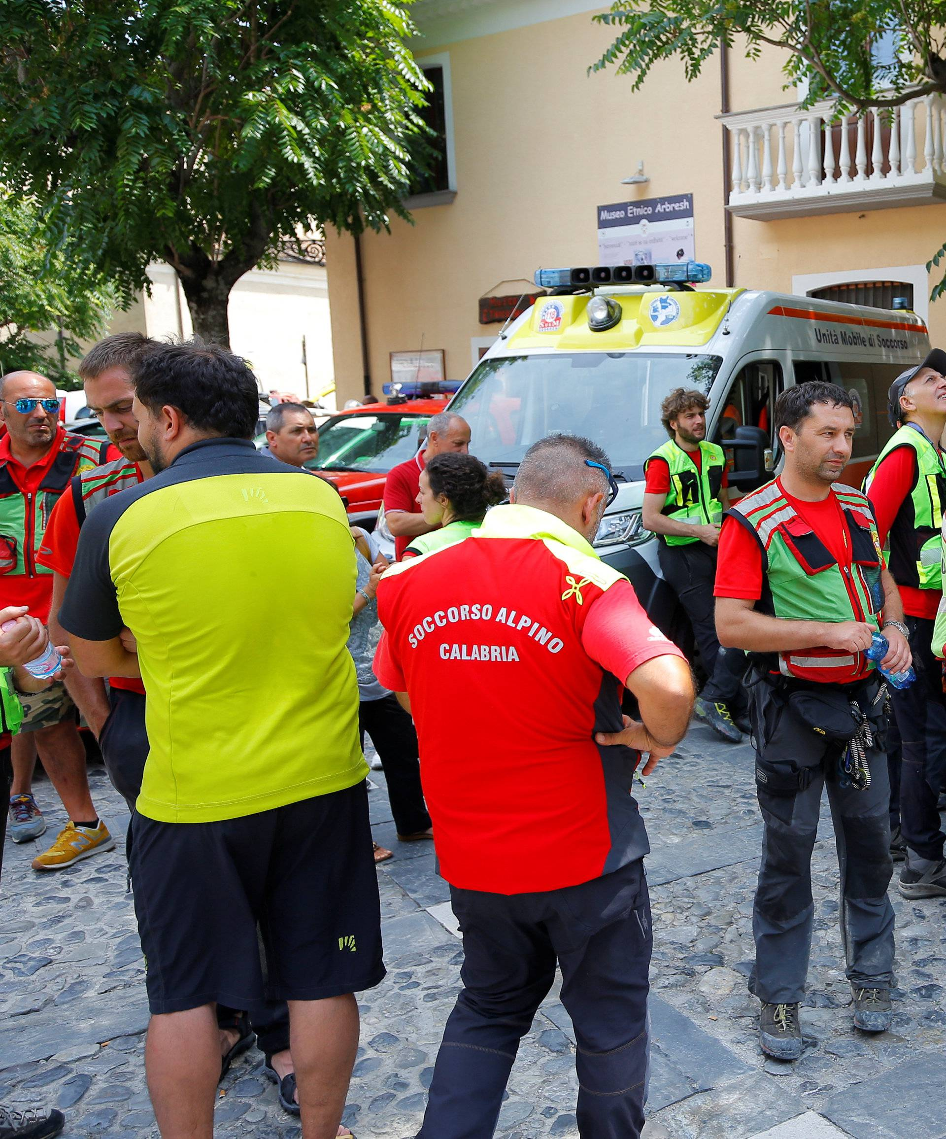 Rescue workers rest in Civita village after several people were killed in a mountain gorge flooding in the area of gorge of Raganello